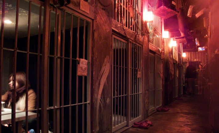 jail cells with tables inside lit with red lamps
