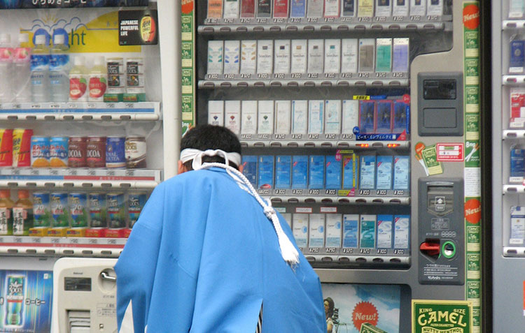Man in Japan purchasing cigarettes at a vending machine