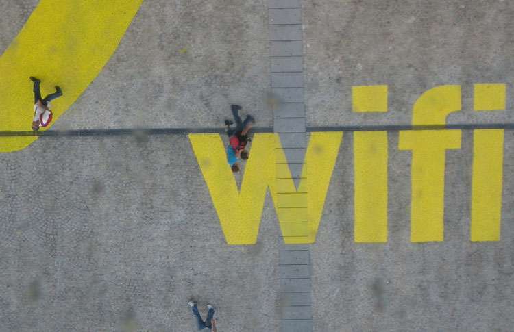 People walking on  the word wifi in yellow block letters