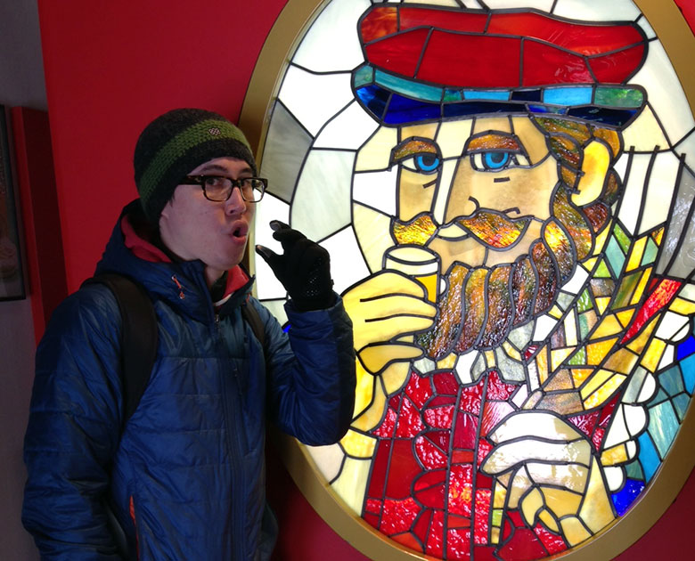 man standing next to stained glass