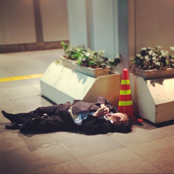 A drunk person passed out on a street corner
