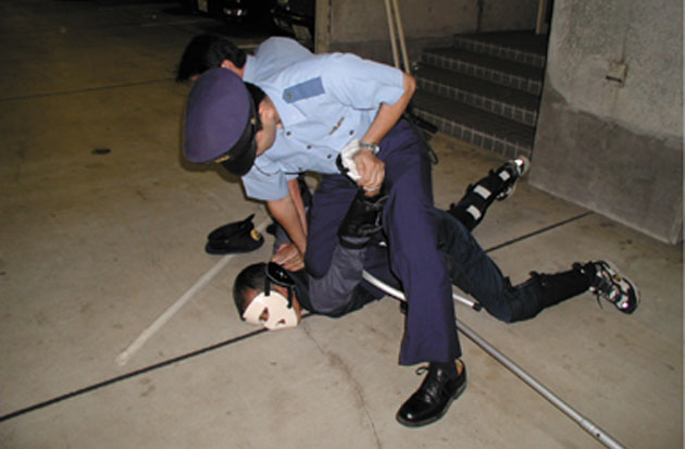 police officer restraining man on the ground