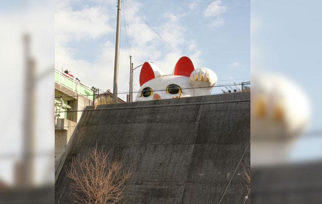 Large Maneki Neko peeking over a wall