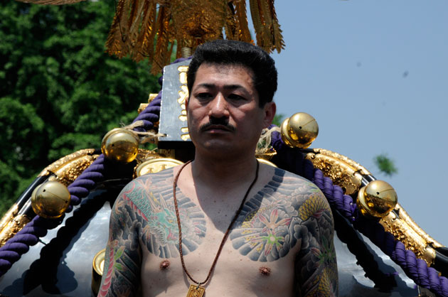 A shirtless Japanese man bearing tattoos