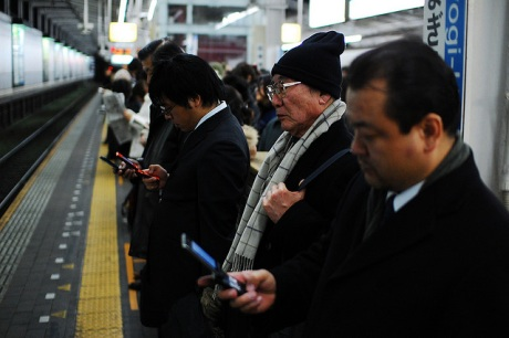 Japanese people lined up in the subway, looking at their phones