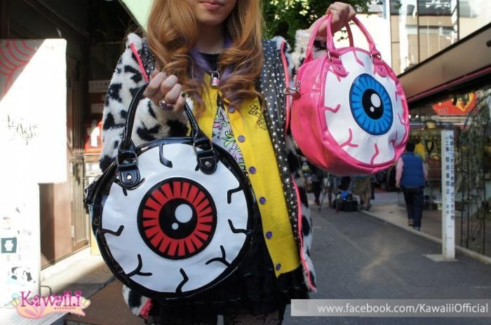 A girl carrying two bags shaped as eyeballs