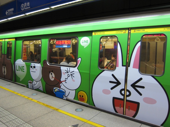 A subway train with an advertisement for LINE
