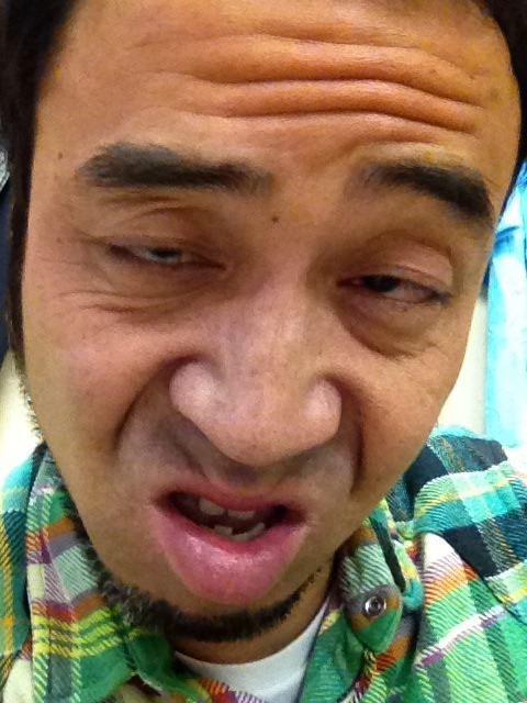 Japanese man makes a weird face while looking tired