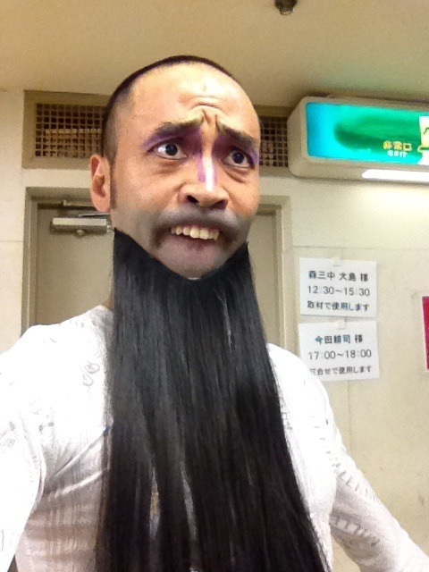 Japanese man makes a weird face while wearing a fake beard and showing his teeth