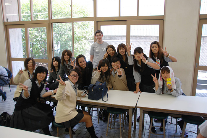 thirteen students from japan at tables posing for the camera