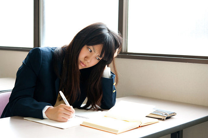 japanese school girl sitting at desk with head propped up