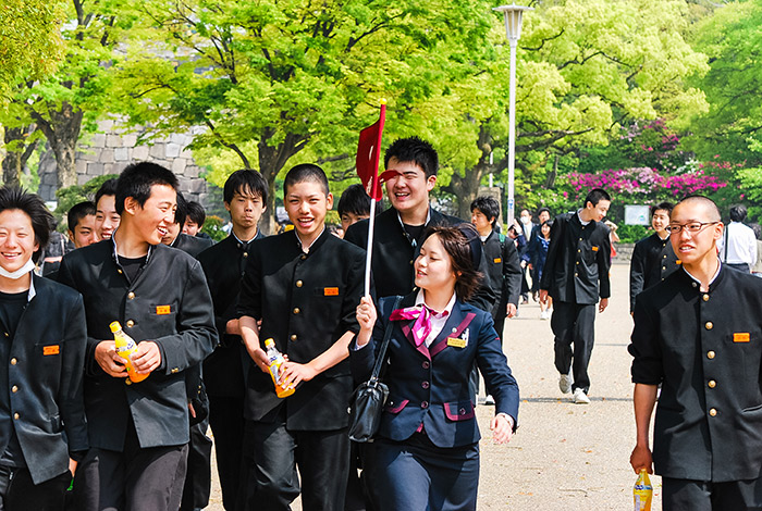 class of japanese students in uniforms following a tour guide