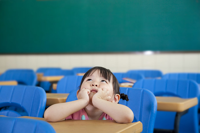 japanese schoolgirl sitting in japanese classroom looking up at ceiling