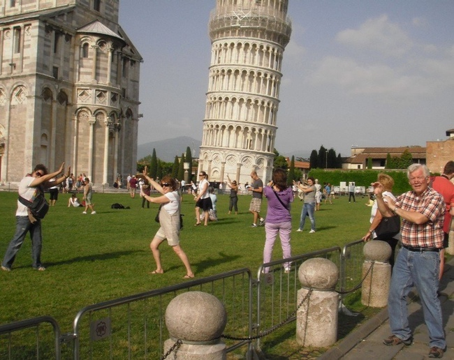 bunch of white people taking the same picture of the leaning tower of pisa