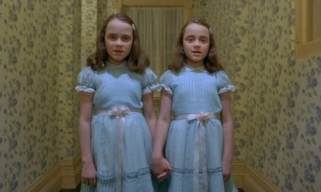 still from the shining two girls standing in a hallway