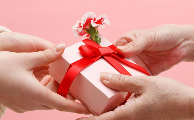 two hands exhanging a present with a flower