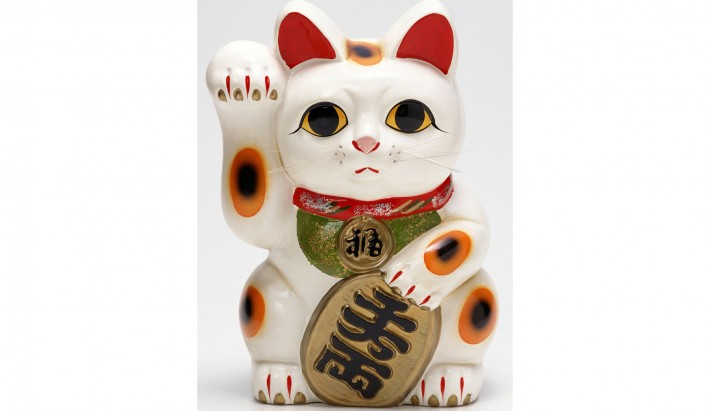 white cat with koban figurine