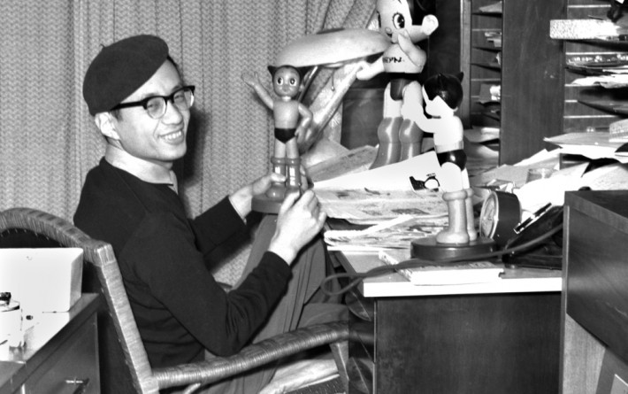 Osamu Tezuka with several statues of Astroboy