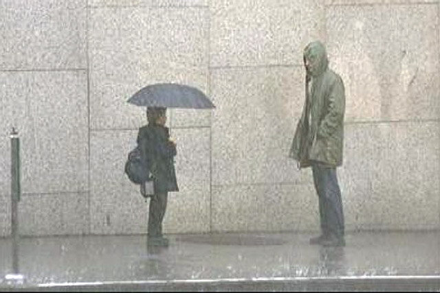 man standing in the rain looking at a kid holding and umbrella