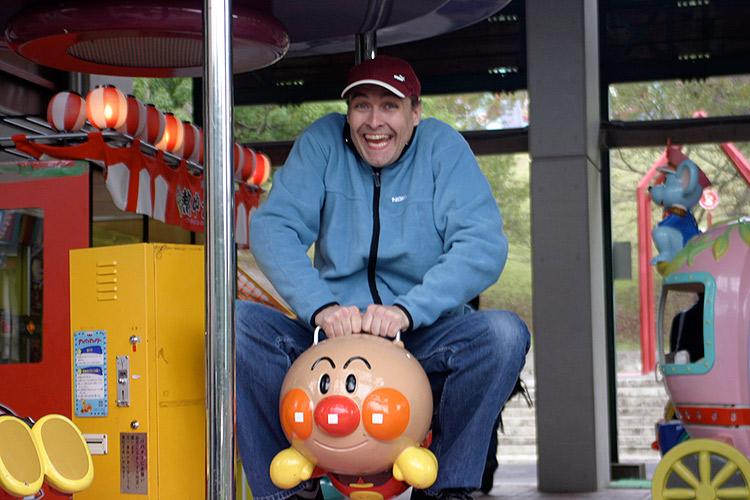 happy foreigner wearing hat is excited about riding anpanman