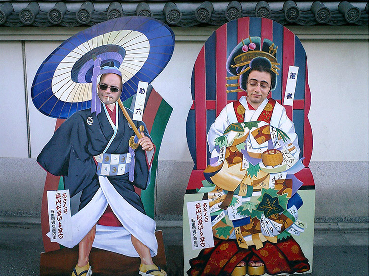 foreigners stand behind large cutouts of traditional Japanese outfits