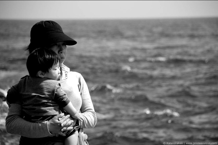 Japanese mother holding child by sea