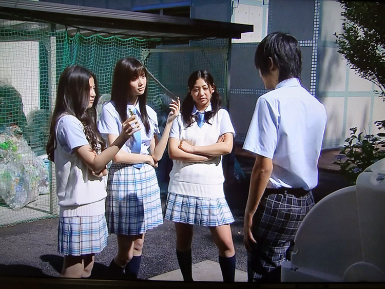 Mean-looking Japanese girls talking to a classmate