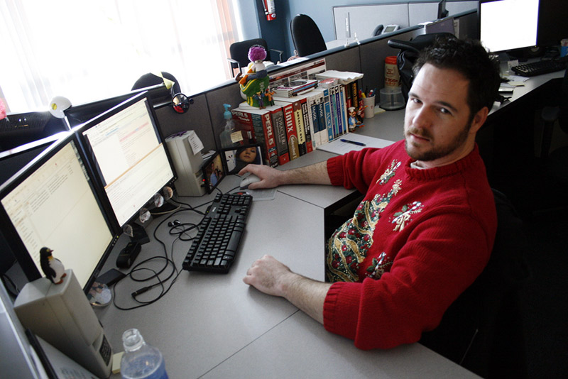 man at cubicle desk with christmas sweater