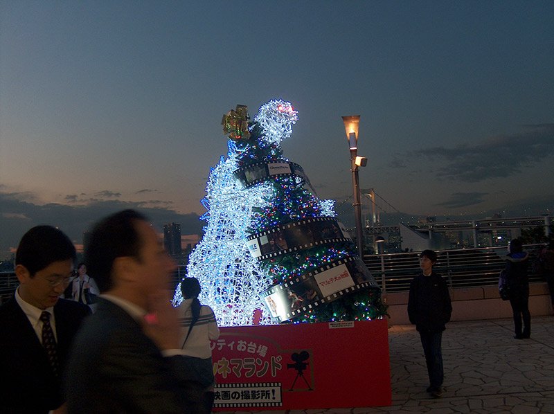 godzilla made of christmas lights attacking tree
