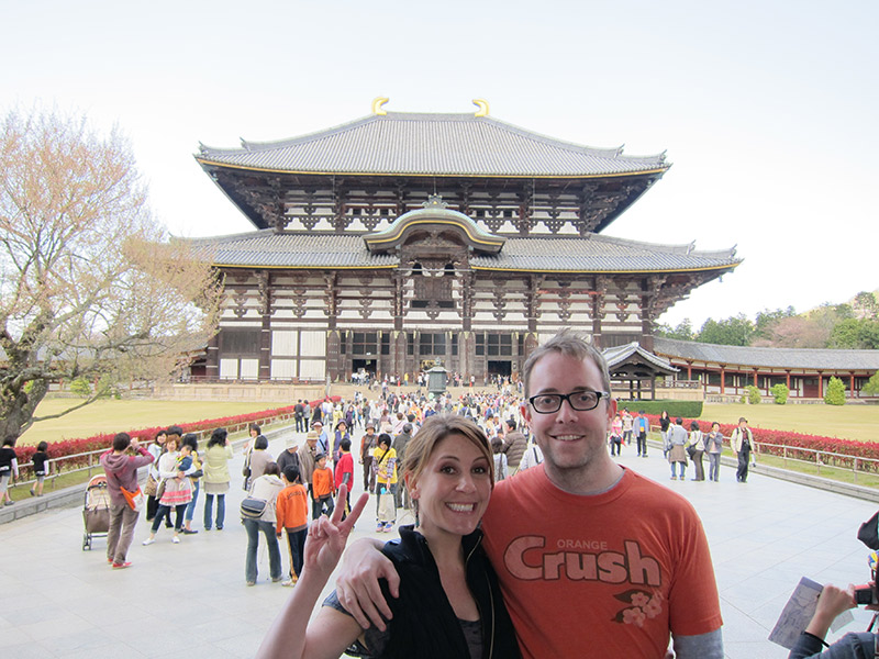 tourist couple posing for photo in front of temple