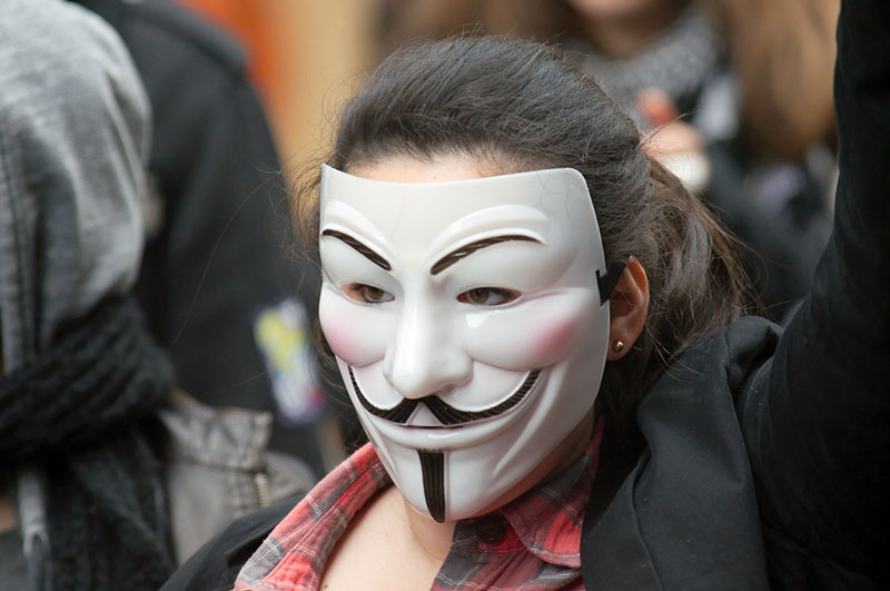 woman wearing Guy Fawkes mask