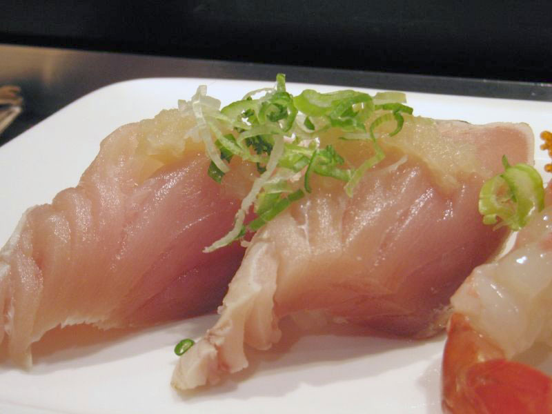 raw white tuna slices on plate with sliced green onion