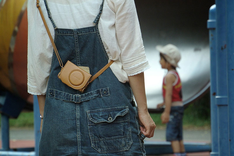 woman in overalls with camera and small boy