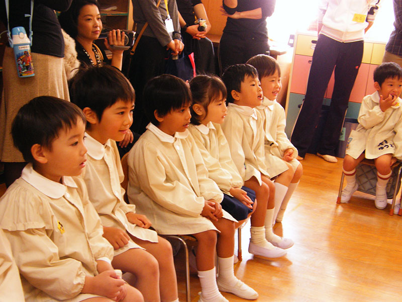 young japanese students in white watching performance