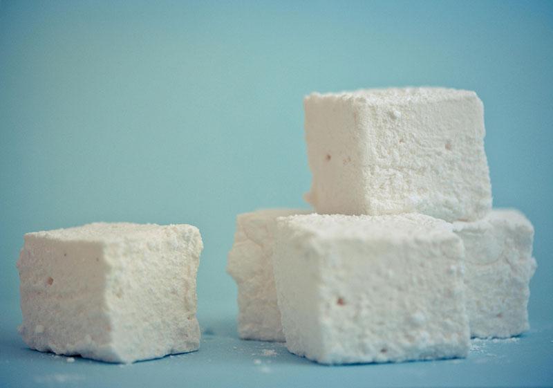 four white marshmallows on a blue background