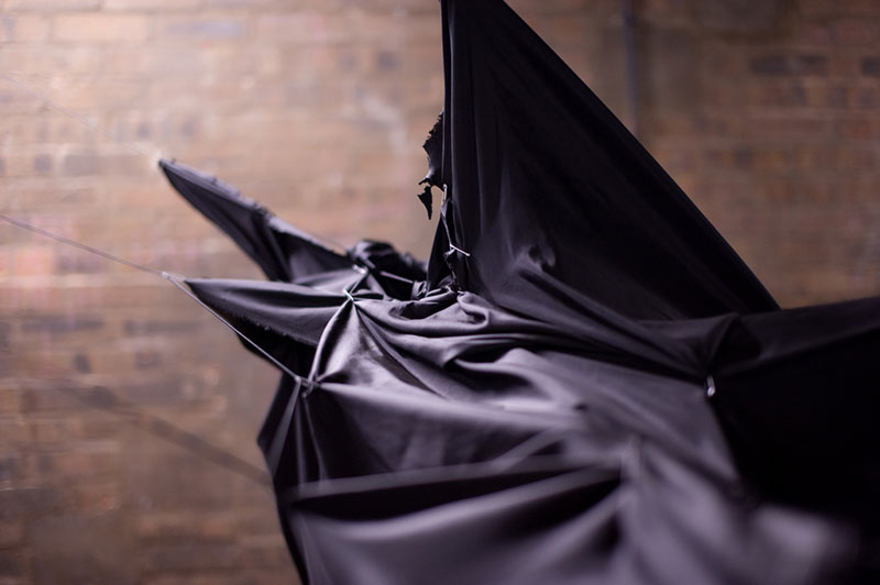 black cloth being hung and pulled at different angles