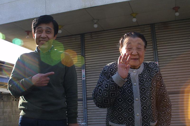 An elderly Japanese couple waving goodbye