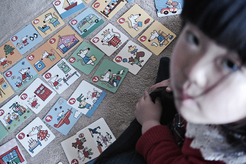 girl in front of cards on the floor