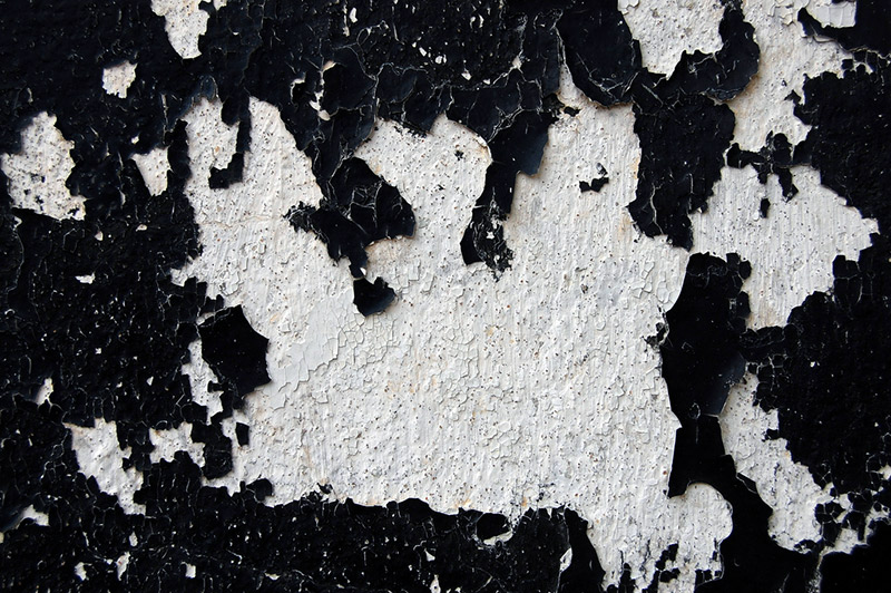 Black paint chipping off a wall