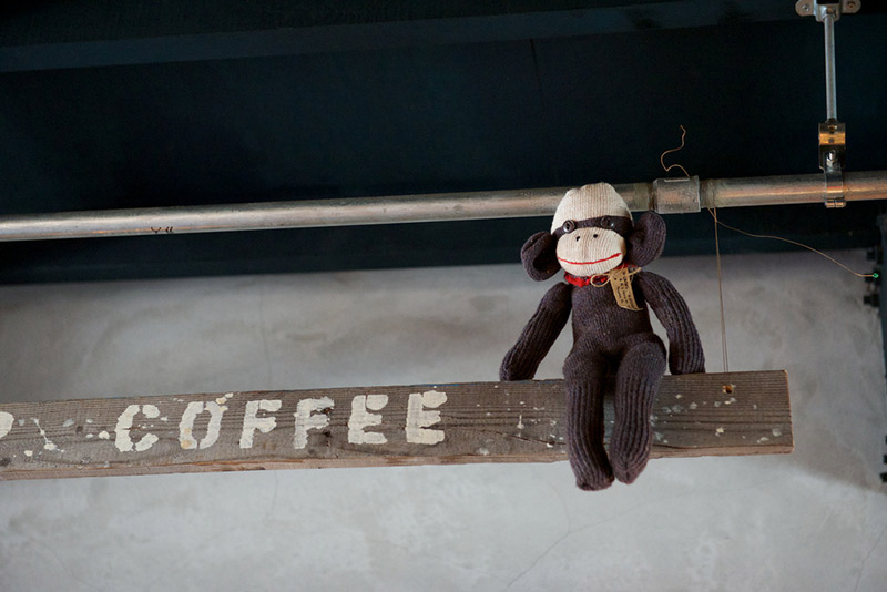 stuffed monkey perched on coffee sign