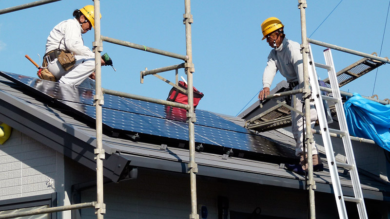 Construction workers installing solar panels on a house
