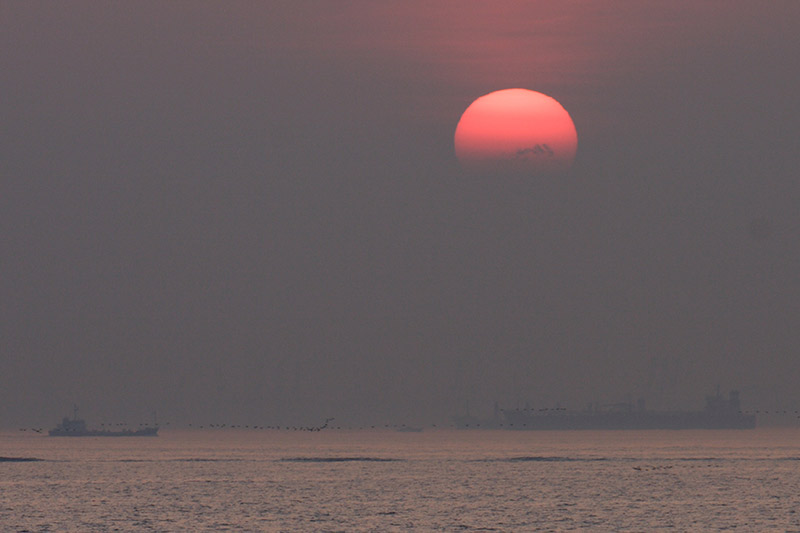 Red sun setting over a hazy sea