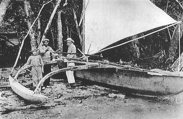 Grainy black and white photo of three men standing by an outrigger canoe