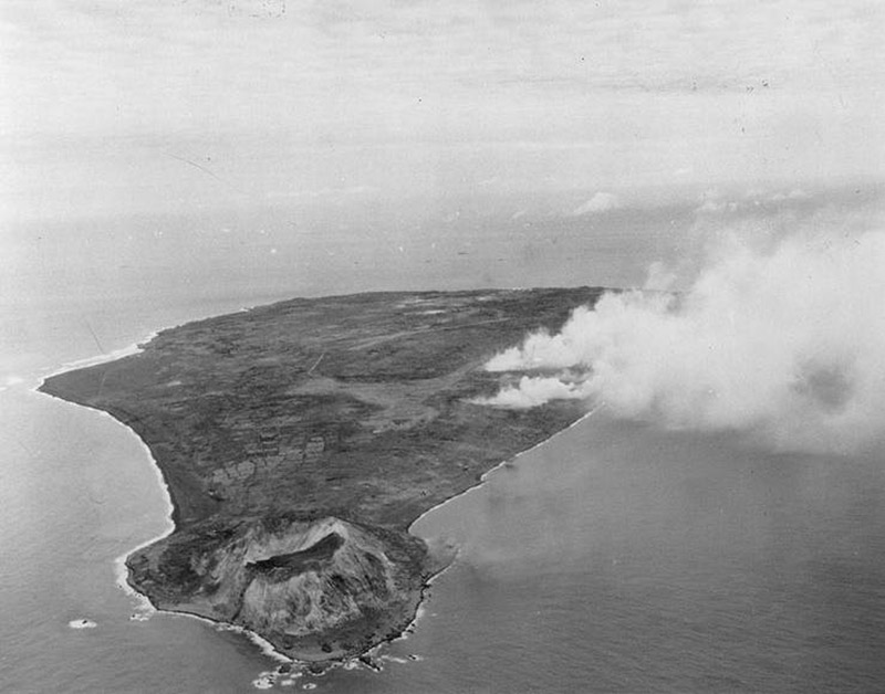 Black and white aerial image of a small island with a crater at one end and smoke rising from somewhere behind it