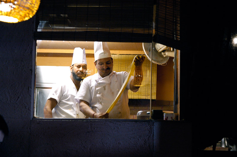 two chefs seen through window of Indian restaurant