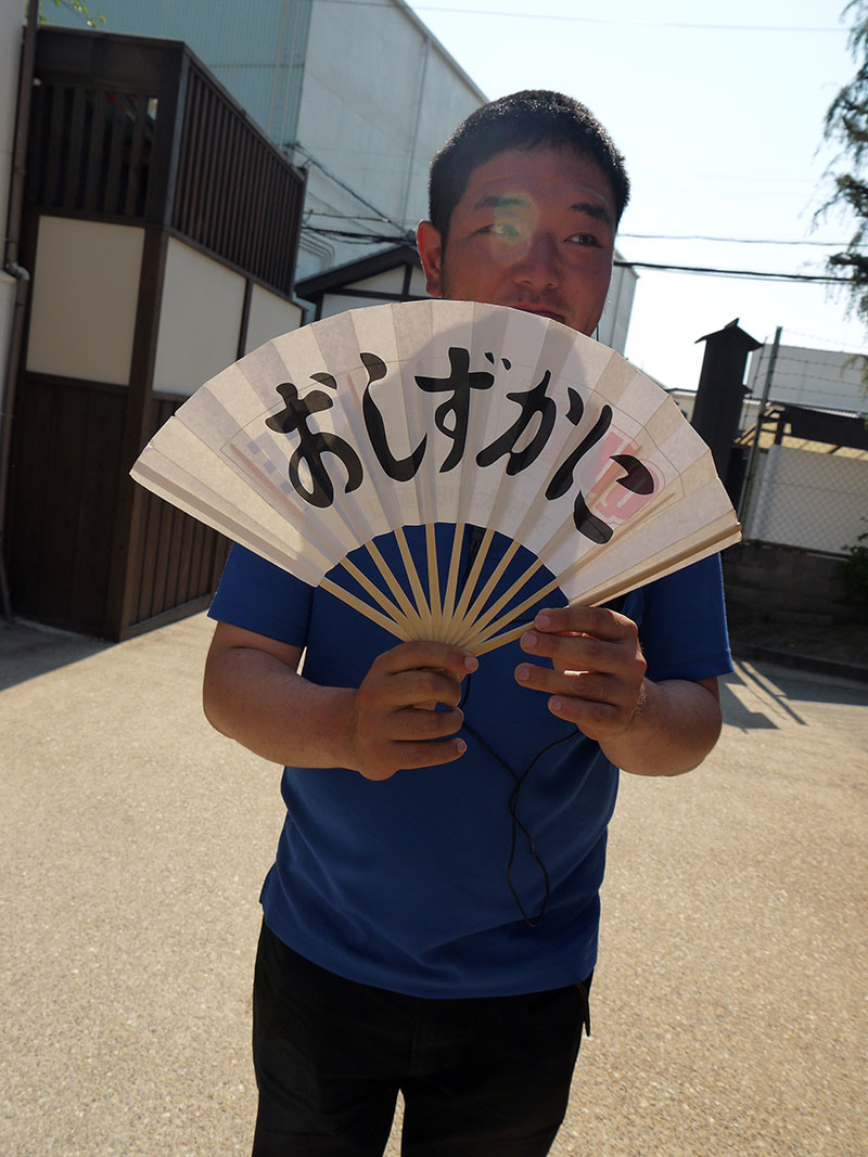 man holding a fan that says quiet please in japanese