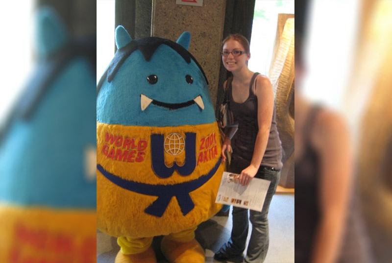 Kristen Dexter standing next to a cute blue ogre mascot
