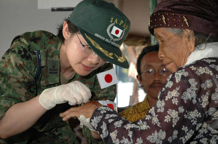 JSDF Personnel assisting an elderly woman in Indonesia