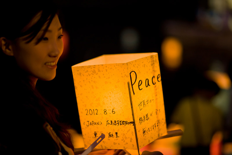 japanese woman holding a lantern that says peace