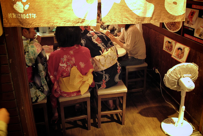 young girls wearing kimonos eating at japanese shop